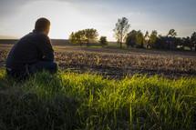 man sitting in a freshly plowed field