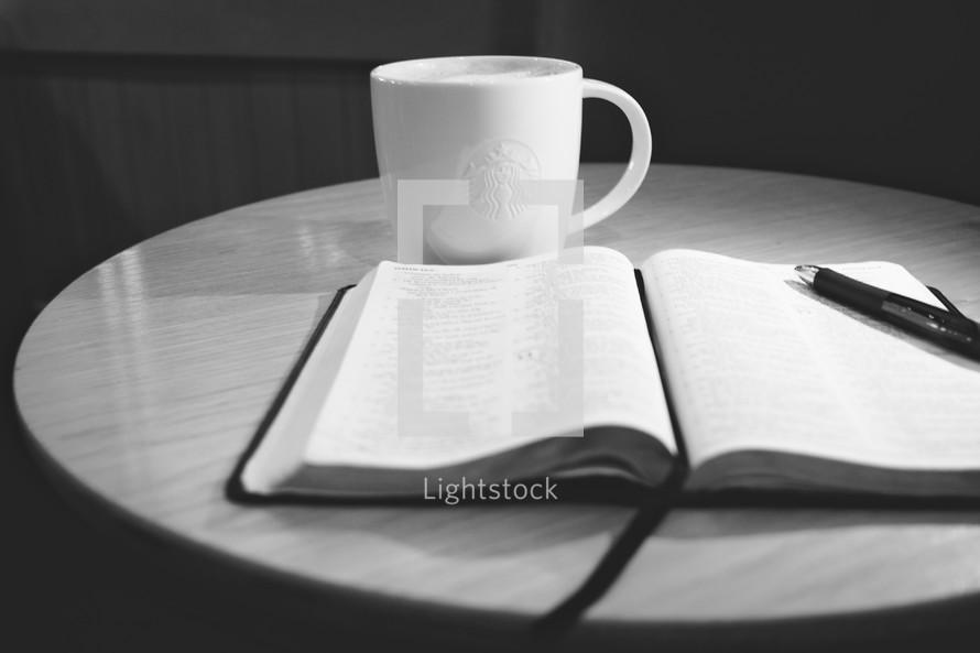 Open bible next to coffee mug