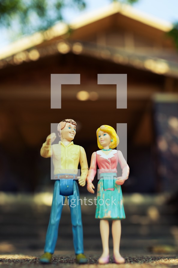 Plastic toy couple in front of a house