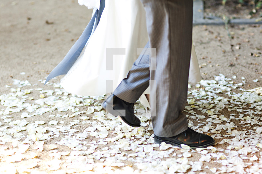Bride and groom walking on flower petals wedding isle I do marriage relationship together