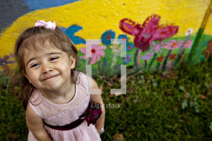 happy little girl standing in front of a painted wall
