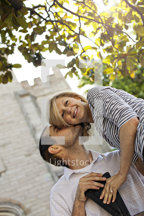 Happy couple sitting in front of old building