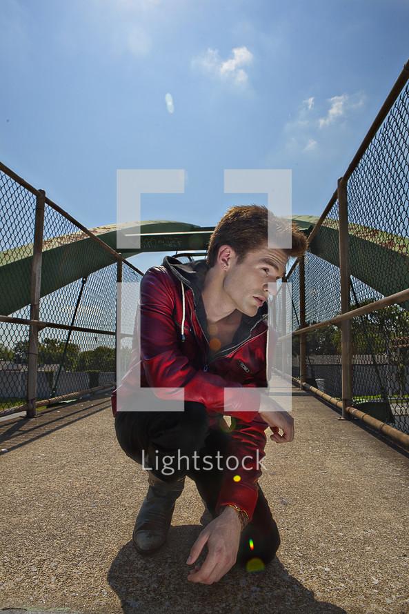 man kneeling on a overpass sidewalk