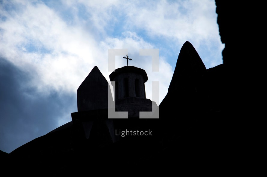 Silhouette of church steeple with cross on top with blue sky and clouds in the background.
