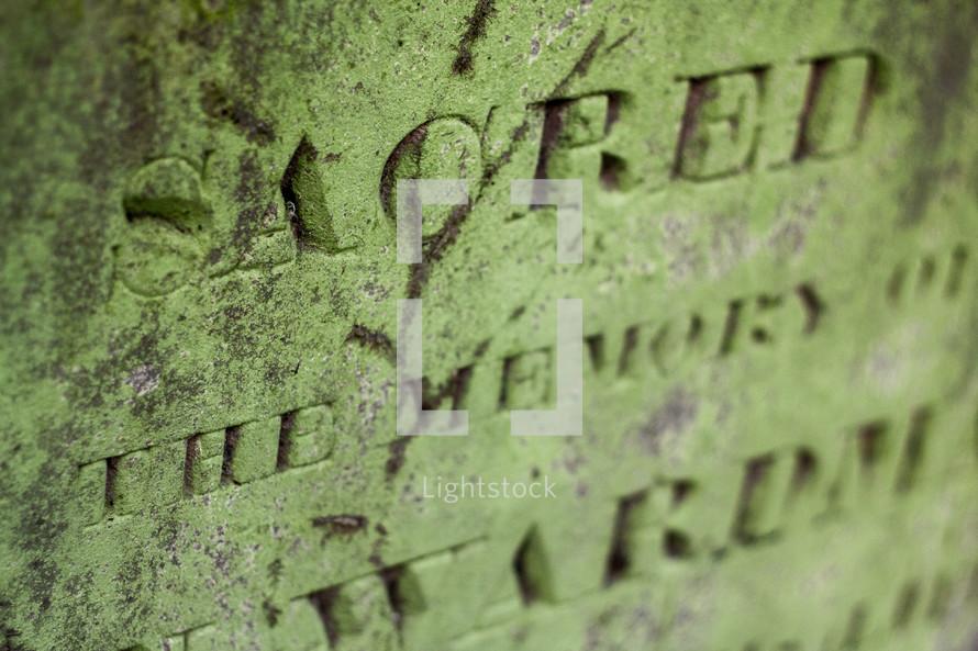words chiseled on stone