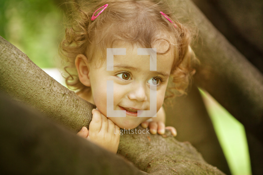 Smiling girl holding onto a limb