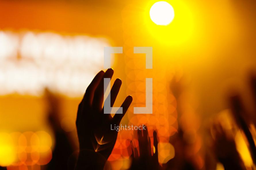 Hands raised in worship orange flare