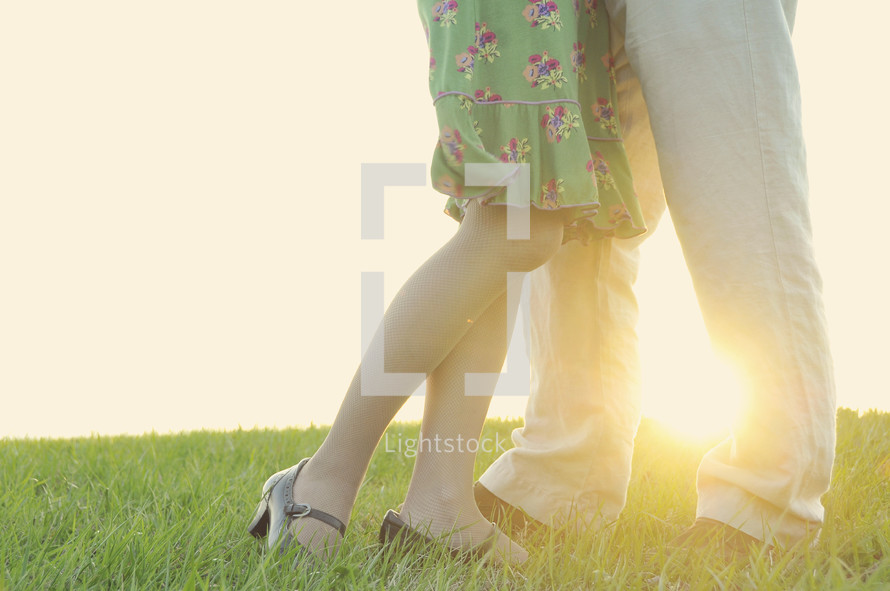Couples legs and shoes standing in grass