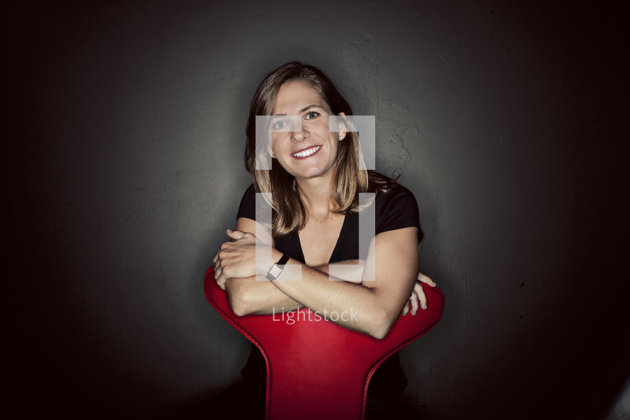 A woman smiling behind a red chair