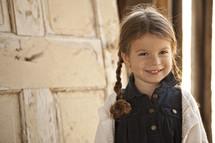 girl child standing in front of a door