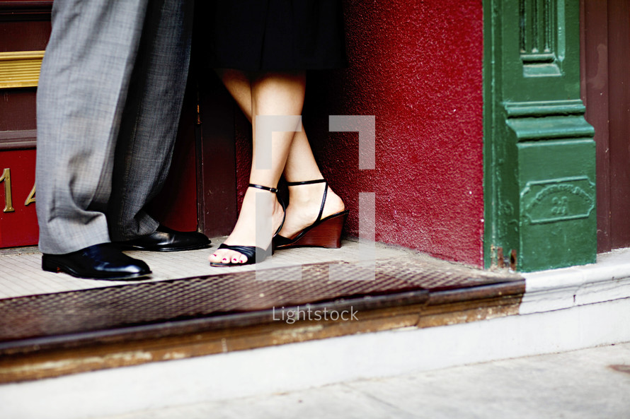 feet of a couple standing in a doorway of city apartment by street heels dress shoes