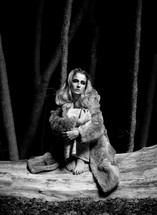 woman sitting on fallen tree wearing a fur coat and holding her legs