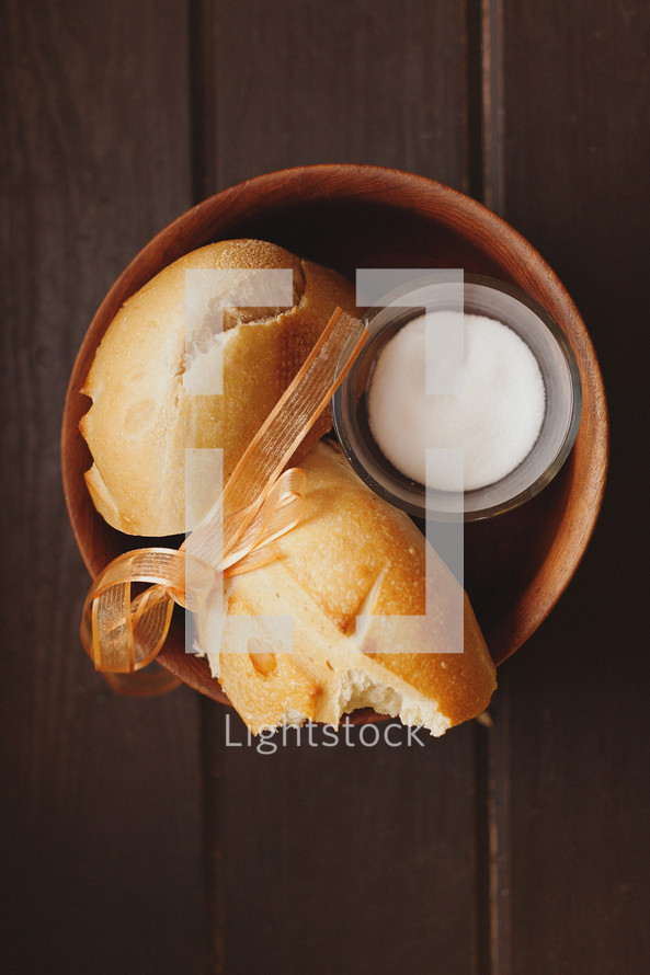 Broken loaf of bread and butter in bowl