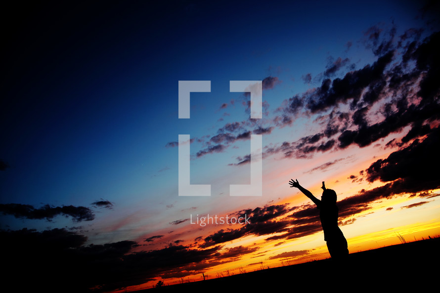 Man with raised hands at sunset
