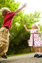 toddler boy and girl reaching for the sky