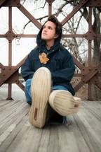 man sitting on a wood walkway waiting