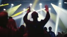 raised hands under spotlights