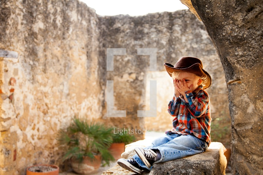 boy sitting on rock in stone building
