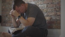 a man sitting on the floor praying with a Bible in his lap