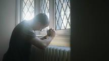 a man praying at a window