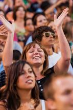 Church service woman raising hands in worship eyes closed crusade