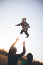 Man throwing toddler child in the air while standing with woman in grassy field at dusk.