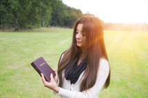 a woman holding a Bible outdoors