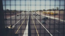 Highway traffic as seen through the cage of a bridge.