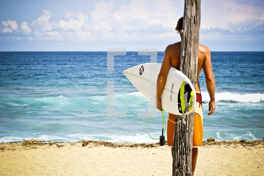 surfer holding a surfboard in front of ice blue water