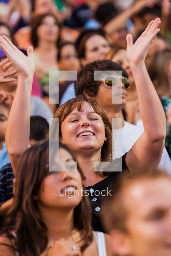 Church service woman raising hands in worship eyes closed crusade