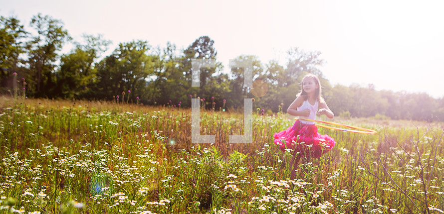 little girl dancing in a field of wild flowers
