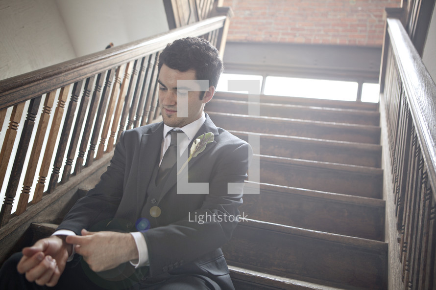 groom sitting in a stair way before his wedding