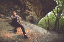 man sitting on a rock ledge