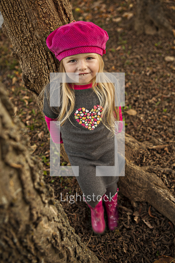 little girl standing in front of a tree trunk