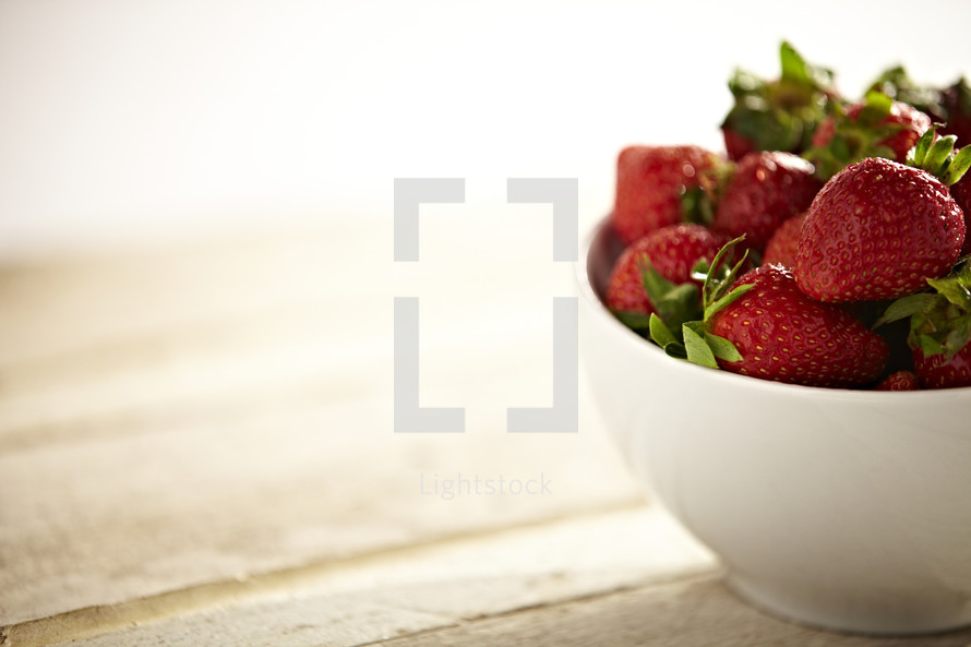 A bowl of strawberries on a table