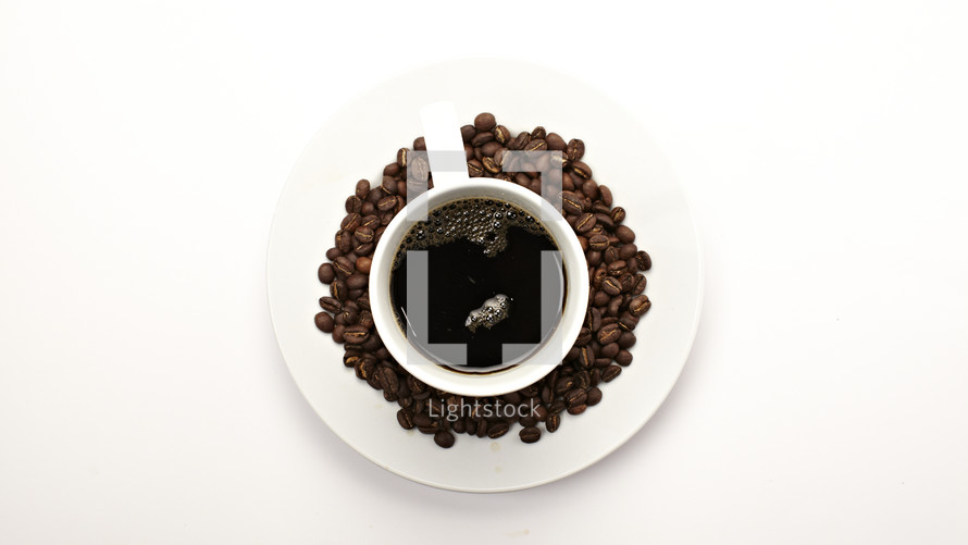 A coffee cup surrounded by coffee beans - isolated on white