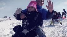 kids sledding down a hill in a village