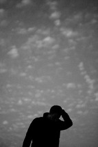 silhouette of a man scratching his head and looking down