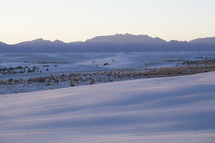 Snow covered tundra with a silhouette of a mountain range on the horizon.