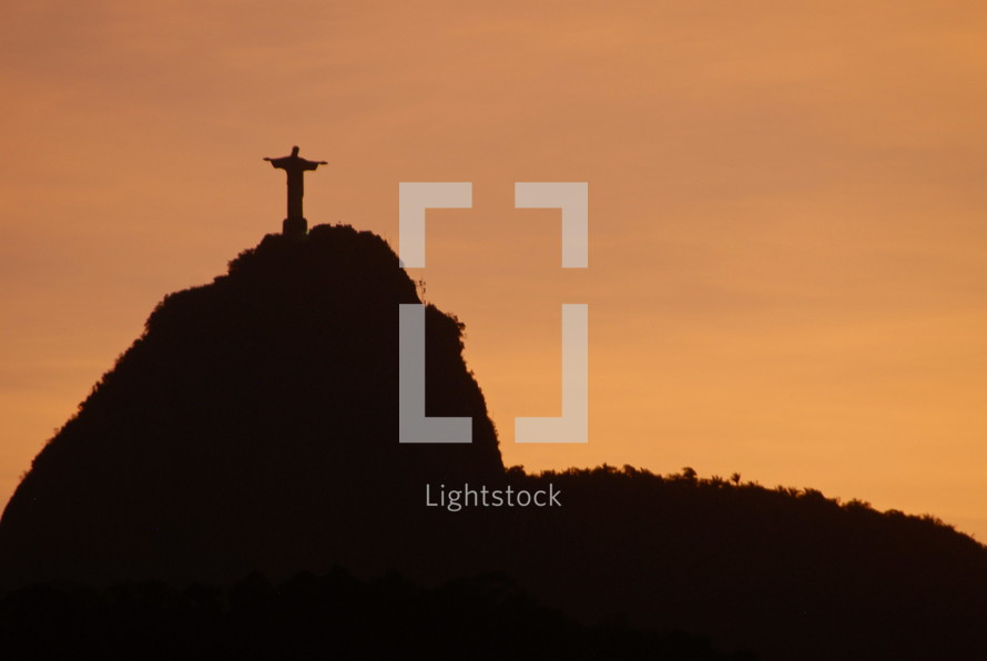 Jesus statue atop a hill at sunset