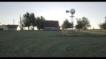 windmill and barn on a farm at sunset