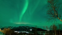 time-lapse of the aurora borealis with clouds moving over a mountain and city lights at night