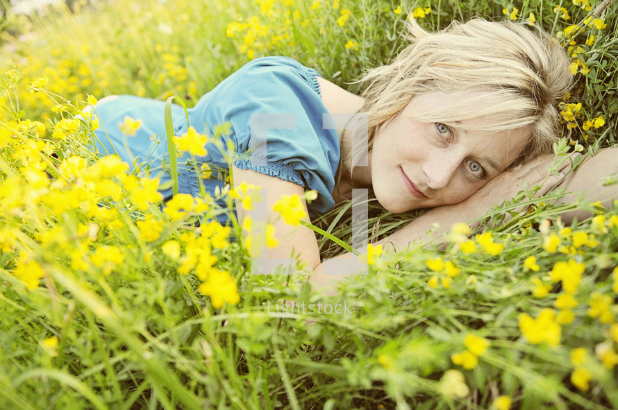 A young woman lying in a field of yellow flowers.