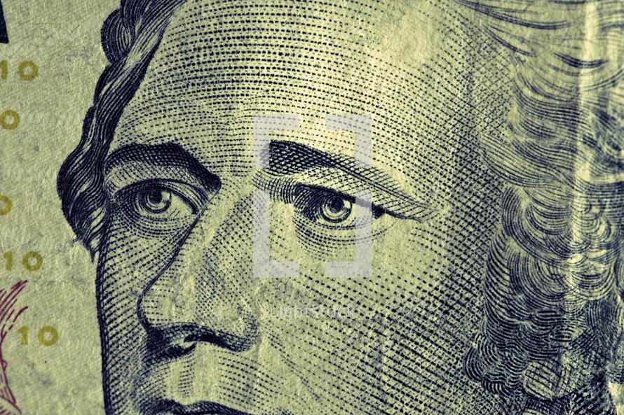 A close up view of Alexander Hamilton on a ten dollar bill