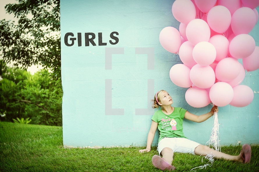 A girl sitting against a blue wall with pink balloons.