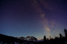 stars in the night sky over snowy mountain peaks