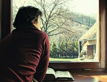 a man reading a Bible and looking out a window
