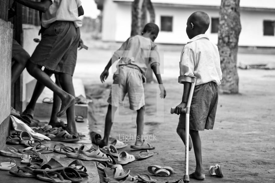 A crippled boy, leaning on his crutch, waits to enter a school