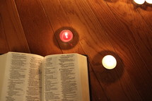 Bible and red and white votive candles