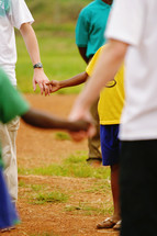 adults and children holding hands in a circle white caucasion black african american